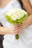 Bröllopgruppen av blommor räcker in bruden Arkivfoton