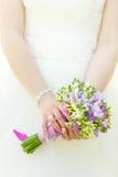 Bröllopgruppen av blommor räcker in bruden Royaltyfri Bild