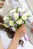 Bröllopgruppen av blommor räcker in bruden Arkivbild