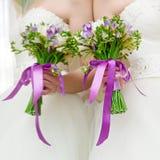 Bröllopgruppen av blommor räcker in bruden Arkivfoto