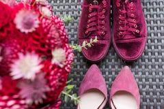 Bröllophäl VS brud- gymnastikskor Brud- tillbehör för rött bröllop: brud- häl och gymnastikskor av marsalaen färgar, röd brud- bu Royaltyfria Foton