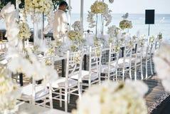 Bröllopmötesplatsen för mottagandematställetabellen som dekoreras med vita orkidér, vita rosor, blommor, blom- vita chiavaristola Arkivbilder