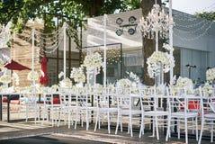 Bröllopmötesplatsen för mottagandematställetabellen som dekoreras med vita orkidér, vita rosor, blommor, blom- vit chiavari, pres Arkivbild