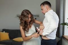 Bröllopmorgon Bruden hjälper hennes fiance att klippa av etiketterna från hennes kläder Begreppet av att att bry sig för älskad Arkivfoton