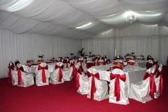 Bröllopordning med vita och röda stolar som väntar på gäster royaltyfri fotografi