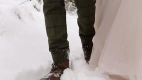 Brölloppar som går i snöig vinterskog under snöfall bukettbruden blommar holdingen Låg vinkel som skjutas av fot