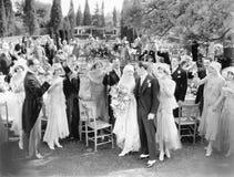 Bröllopparti som rostar till bruden och brudgummen (alla visade personer inte är längre uppehälle, och inget gods finns Leverantö Arkivfoton