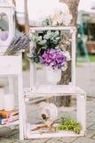Bröllopsammansättning av de vita träspjällådorna med vasen av färgglade blommor i den Spjällådorna dekoreras med Royaltyfri Bild