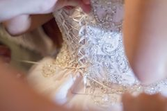 Bröllopsklänning av bruden som binder en korsett Royaltyfria Foton