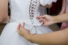 Bröllopsklänning av bruden som binder en korsett Arkivbild