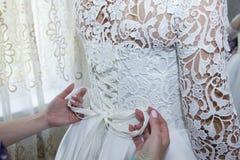 Bröllopsklänning av bruden som binder en korsett Royaltyfri Bild