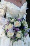 Bröllopsklänning- och bröllopbukett Arkivbild