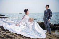 Bröllopsklänning och dräkt för asiatiska par bärande Royaltyfri Bild