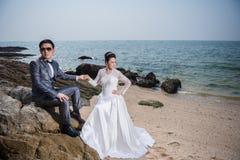 Bröllopsklänning och dräkt för asiatiska par bärande Royaltyfria Foton