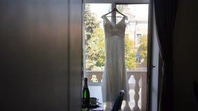 Bröllopsklänning som hänger i ett fönster arkivfilmer