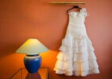 Bröllopsklänning som hänger i rum Arkivbild