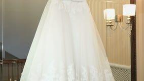 Bröllopsklänning som inomhus hänger på skuldror stock video