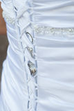 Bröllopsklänningbaksida snör åt med vigselringar Arkivbild