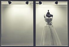 Bröllopsklänningen i fönstret av shoppar royaltyfri foto