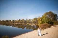 Bröllopsresa av precis gifta brölloppar lycklig brud, brudgumanseende på stranden och att kyssa och att le och att skratta och at Royaltyfri Bild