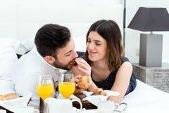 Bröllopsresapar som har frukosten i hotellrum Fotografering för Bildbyråer