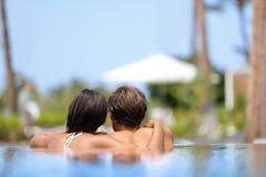 Bröllopsresapar som tillsammans kopplar av - simbassängen Royaltyfri Bild