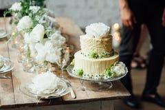 Bröllopstårta dekorerad vindstil med en tabell och tillbehör royaltyfri bild