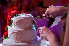 Bröllopstårta för nygift personhandsnitt royaltyfri fotografi