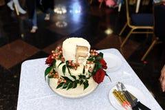 Bröllopstårta med ett klippt stycke på en vit bordduk royaltyfria foton