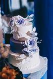 Bröllopstårta med gula beigea röda blått för blommor royaltyfri fotografi