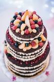 Bröllopstårta med gula beigea röda turkosblått för frukter royaltyfri fotografi