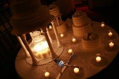 Bröllopstårta med stearinljus och knivar Arkivfoto