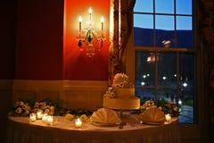 Bröllopstårta på tabellen med stearinljus Arkivfoto
