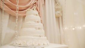 Bröllopstårta som dekoreras med rosor, ställningar på en trätabell close upp Glid kameran lager videofilmer
