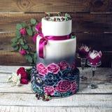 Bröllopstårta som smyckas i lantliga blåa och purpurfärgade rosor för stil Royaltyfri Bild