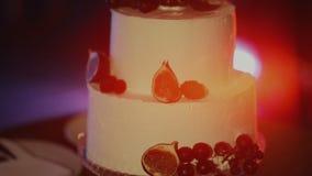 Bröllopstårtacloseup Härlig kaka med bär, kräm läcker cake Kakan ligger på ställningen, på plattan arkivfilmer
