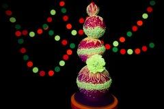 Bröllopstårtan för UV fotografi för neon glöder den ljusa färgrika fluorescerande färger på en mörk bakgrund i strålarna av arkivbilder