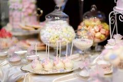 Bröllopstårtan poppar i rosa färger och lilor Arkivfoto