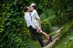 Brölloptema Brudgummen kysser bruden i en botanisk trädgård Royaltyfri Fotografi