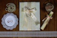 Brölloptillbehör och inbjudningar för att inrama den ljusa trätabellen Arkivfoto