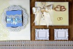 Brölloptillbehör och inbjudningar för att inrama den ljusa trätabellen Arkivfoton