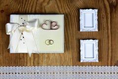 Brölloptillbehör och inbjudningar för att inrama den ljusa trätabellen Fotografering för Bildbyråer