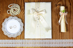 Brölloptillbehör och inbjudningar för att inrama den ljusa trätabellen Royaltyfri Foto