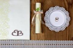 Brölloptillbehör och inbjudningar för att inrama den ljusa trätabellen Royaltyfria Foton