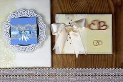 Brölloptillbehör och inbjudningar för att inrama den ljusa trätabellen Royaltyfria Bilder