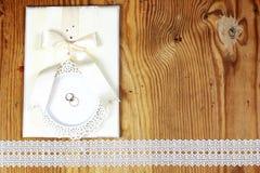 Brölloptillbehör och inbjudningar för att inrama den ljusa trätabellen Royaltyfri Fotografi