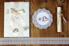 Brölloptillbehör och inbjudningar för att inrama den ljusa trätabellen Arkivbilder