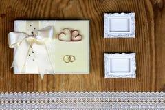 Brölloptillbehör och inbjudningar för att inrama den ljusa trätabellen Royaltyfri Bild