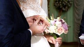 Brölloptraditioner, ceremonier bröllop för brudceremoniblomma nygifta personer bär sig cirklar på cirkelfingrarna Närbild stock video