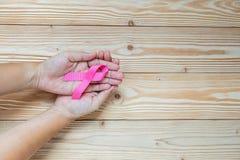 Bröstcancermedvetenhet, hållande rosa band för kvinnahand royaltyfri fotografi
